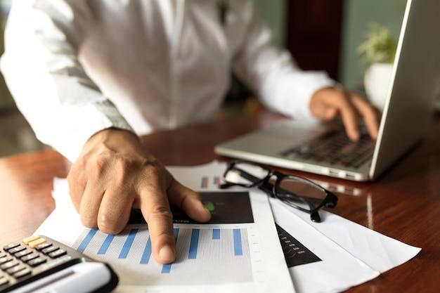 Empresário, trabalhando com o local de trabalho moderno com o laptop na mesa de madeira, mão de homem no teclado do laptop para o trabalho de casa,