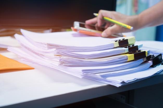 Empresário, trabalhando em arquivos de papel de pilhas