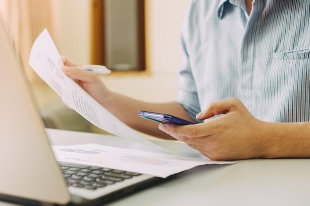Empresário trabalhando em casa escritório com telefone inteligente e computador portátil.