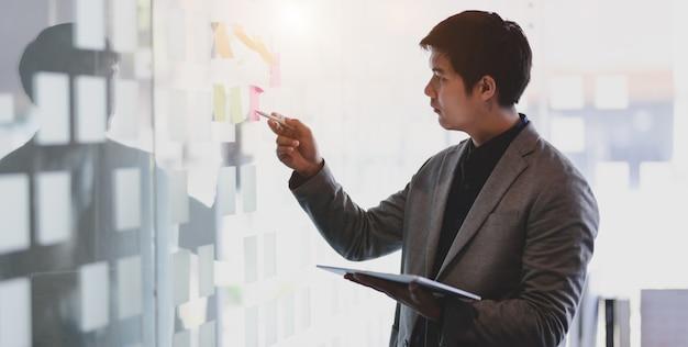 Empresário, trabalhando em seu projeto enquanto pegava a ideia de notas autoadesivas