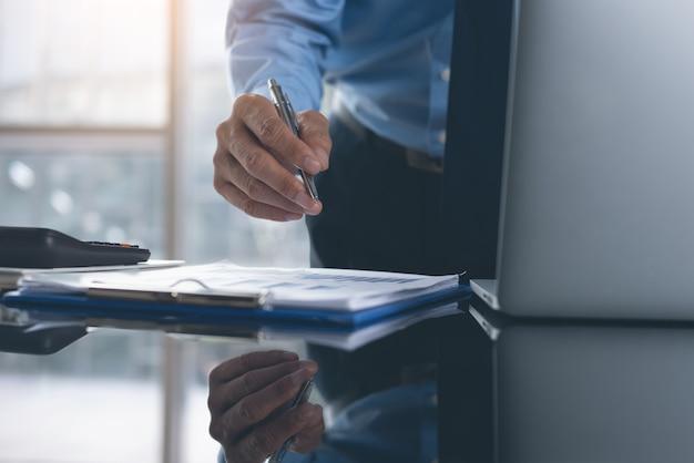 Empresário trabalhando em um laptop com um documento comercial na mesa do escritório