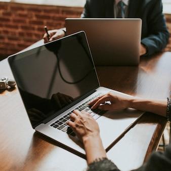 Empresário trabalhando em um laptop em uma reunião de diretoria