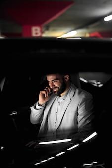 Empresário trabalhando falando sentado em um carro na garagem.