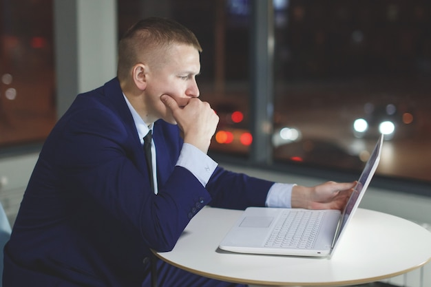 Empresário, trabalhando na mesa com o laptop à noite no escritório. do lado de fora da janela estão acesas luzes multicoloridas