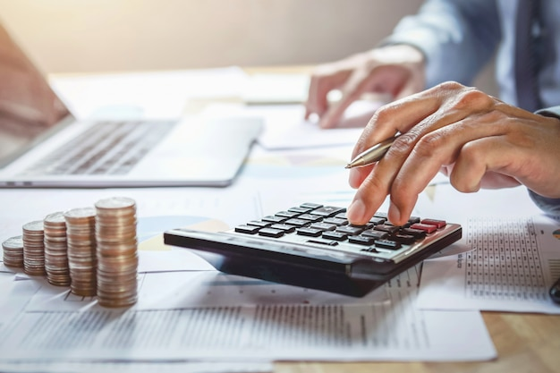 Empresário, trabalhando na mesa com o uso de calculadora para calcular finanças e contabilidade no escritório