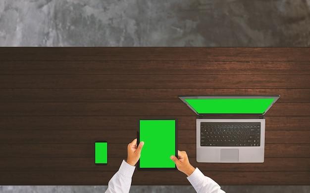 Empresário trabalhando na mesa de escritório com tela verde de smart phone, tablet e laptop.