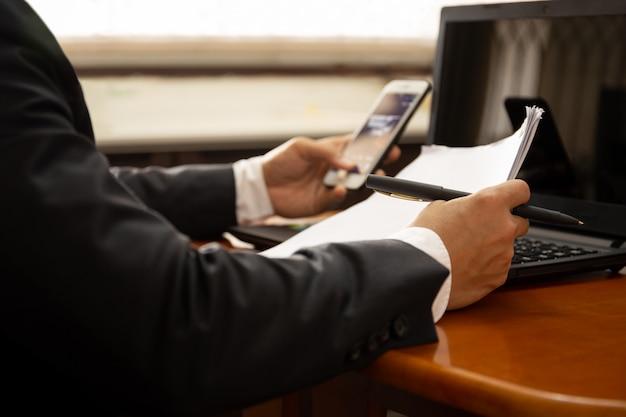 Empresário, trabalhando no documento papel usando telefone celular e laptop.
