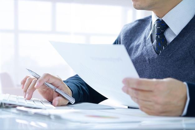 Empresário, trabalhando no escritório, empurrando o teclado do computador, revendo algumas informações sobre o trabalho de rotina.