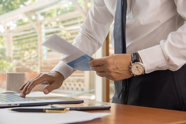 Empresário, trabalhando no laptop com documentos de documentos.