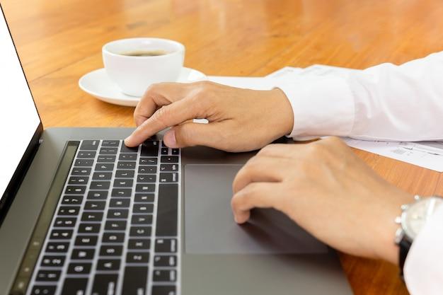 Empresário trabalhando no laptop com papelada na mesa