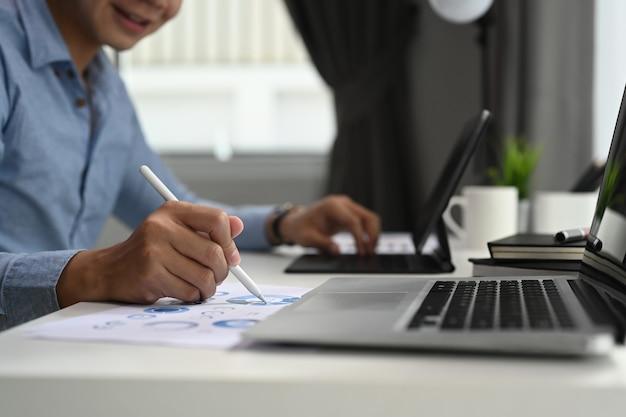 Empresário trabalhando no laptop e analisando dados de negócios no escritório em casa.
