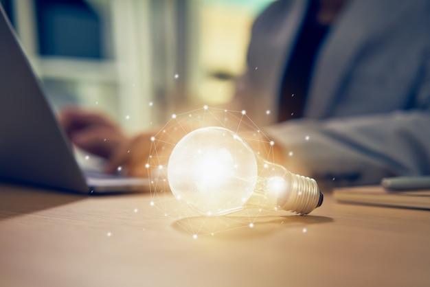 Empresário, trabalhando no laptop e lâmpada em cima da mesa com inovação e criatividade são as chaves para o sucesso.