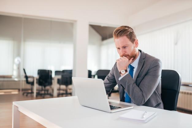 Empresário, trabalhando no laptop no escritório, estar em causa.