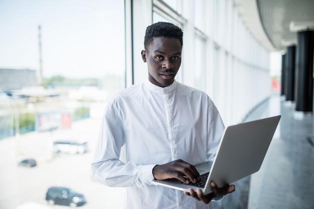 Empresário trabalhando no laptop no escritório moderno