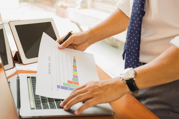 Empresário, trabalhando no relatório financeiro com o laptop na mesa