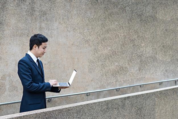 Empresário usa laptop ao ar livre
