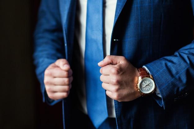 Empresário usa uma jaqueta, mãos masculinas closeup, noivo se preparando a manhã antes da cerimônia de casamento