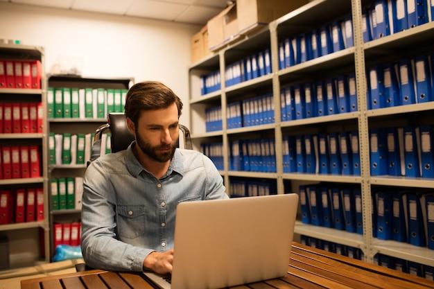 Empresário usando laptop na sala de armazenamento de arquivos