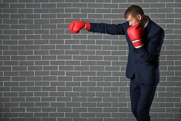 Empresário usando luvas de boxe contra parede de tijolos