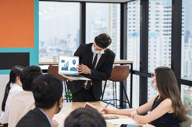 Empresário usando máscara facial com apresentação do plano de negócios no laptop