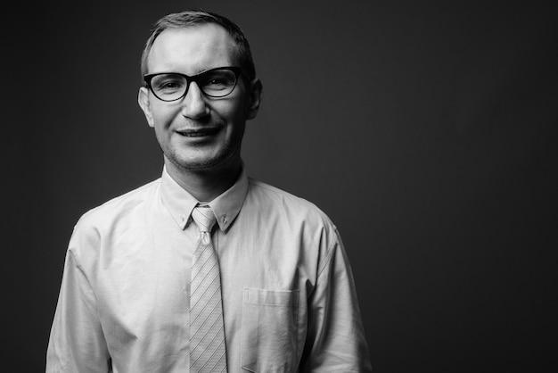 Empresário usando óculos contra a parede cinza em preto e branco
