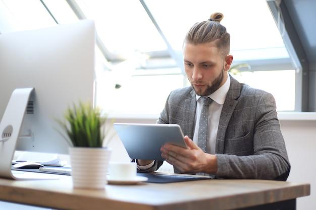 Empresário usando seu tablet no escritório.