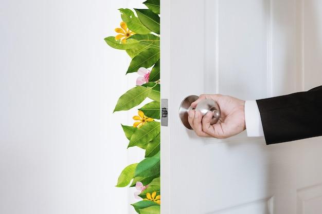 Empresário verde e ecológico abrindo a porta com folhas e flores