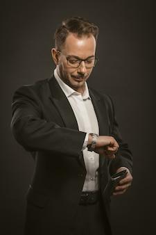 Empresário verifica o tempo olhando para o relógio de pulso.