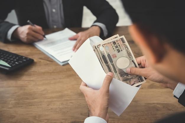 Empresário, verificando dinheiro ienes japoneses no envelope