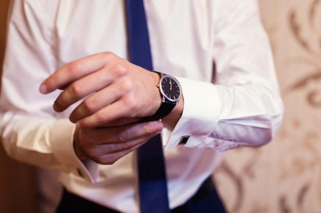 Empresário, verificando o tempo em seu relógio de pulso, homem colocando o relógio na mão, noivo se preparando a manhã antes da cerimônia de casamento
