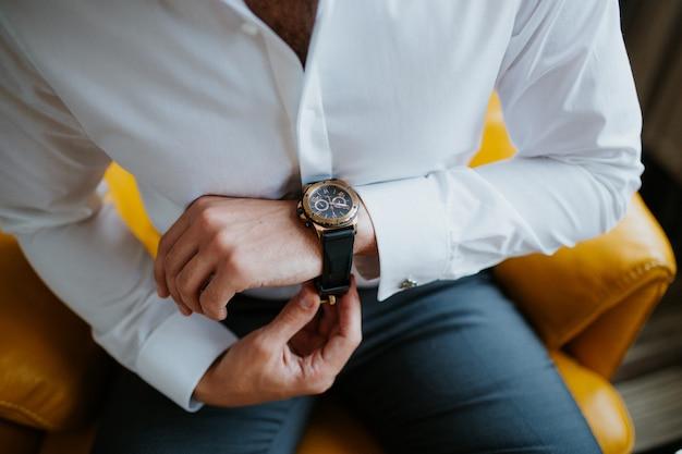 Empresário verificando o tempo em seu relógio de pulso, homem colocando o relógio na mão, noivo se preparando no