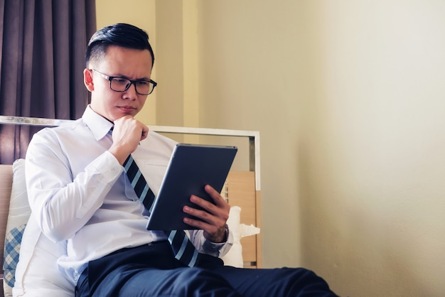 Empresário verificar tablet na cama do hotel