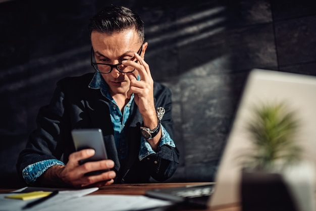 Empresário vestindo óculos usando telefone inteligente