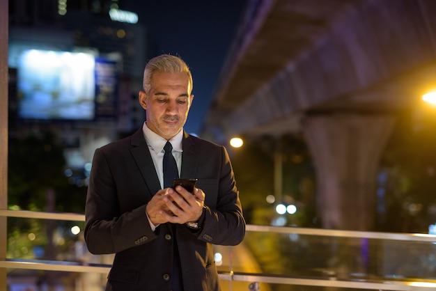 Empresário vestindo terno na cidade à noite enquanto usa o telefone celular