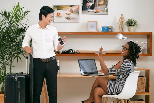 Empresário vietnamita alegre acenando com um colega de trabalho sorridente com bagagem, saindo para uma viagem de negócios