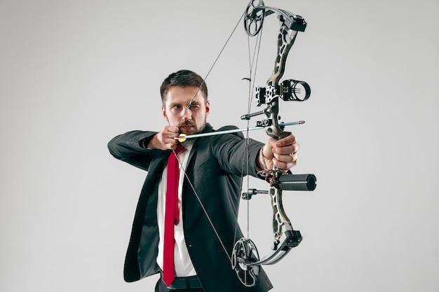 Empresário visando o alvo com arco e flecha, isolado em fundo cinza.
