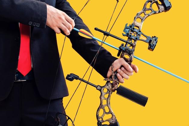Empresário visando o alvo com arco e flecha, isolado no fundo amarelo do estúdio. o negócio, objetivo, desafio, competição, conceito de realização