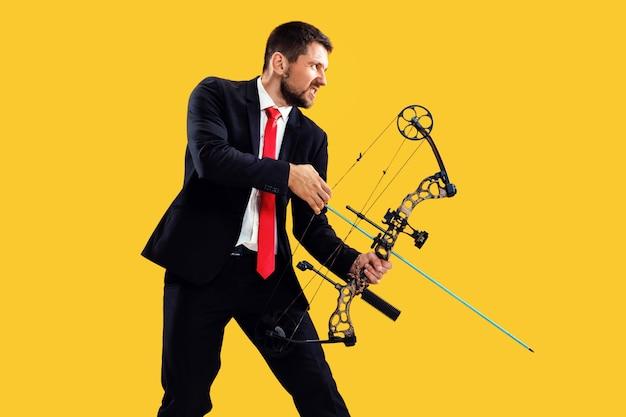 Empresário visando o alvo com arco e flecha, isolado no fundo amarelo do estúdio.