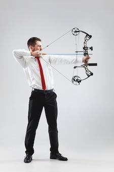 Empresário visando o alvo com arco e flecha, isolado no fundo cinza do estúdio. o negócio, objetivo, desafio, competição, conceito de realização