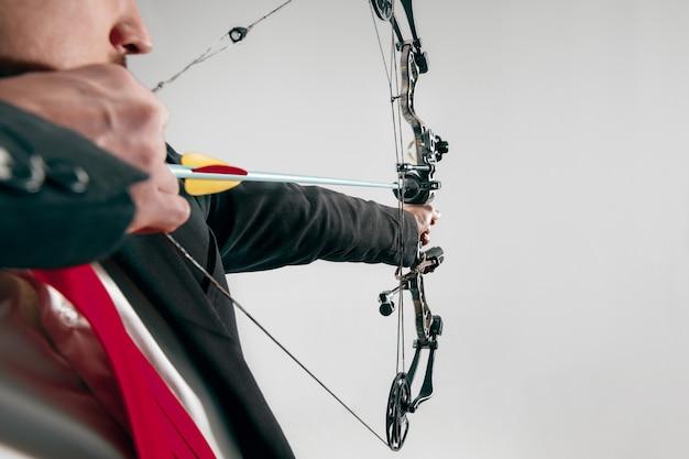 Empresário visando o alvo com arco e flecha, isolado no fundo cinza do estúdio.