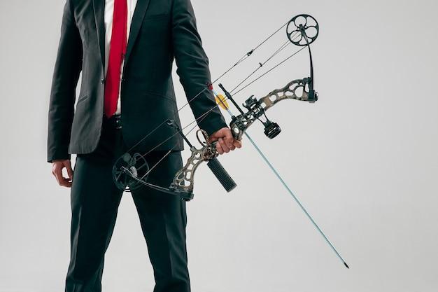 Empresário visando o alvo com arco e flecha isolados no fundo cinza do estúdio. o negócio, objetivo, desafio, competição, realização, propósito, vitória, vitória, clareza, vencedor e conceito de sucesso