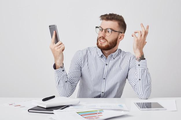 Empresário zangado com um penteado moderno, usa óculos redondos e olha furiosamente para o celular