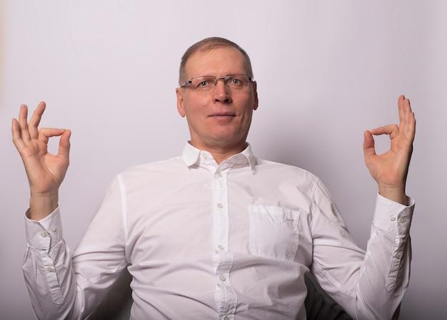 Empresário zen mostrando sinais de ok, sorria e medite.