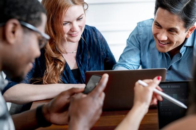 Empresários alegres usando laptops no trabalho