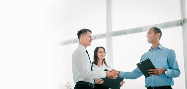 Empresários amigáveis apertando as mãos no fundo desfocado