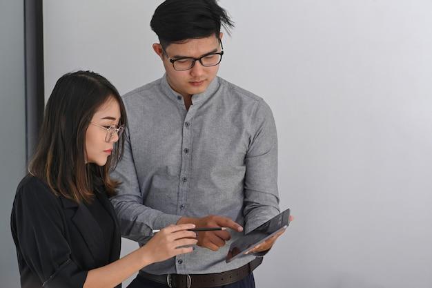 Empresários analisando gráficos e relatórios de mercado juntos em um escritório moderno.