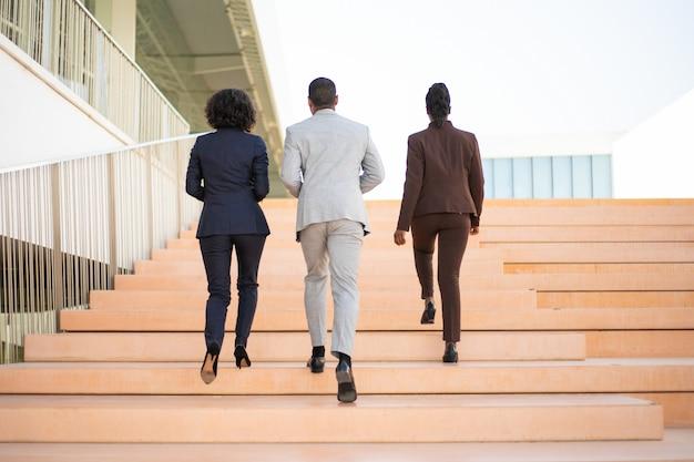 Empresários andando perto do prédio de escritórios