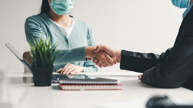 Empresários apertando a mão fazem um acordo para trabalhar juntos com sucesso usam uma máscara no escritório.