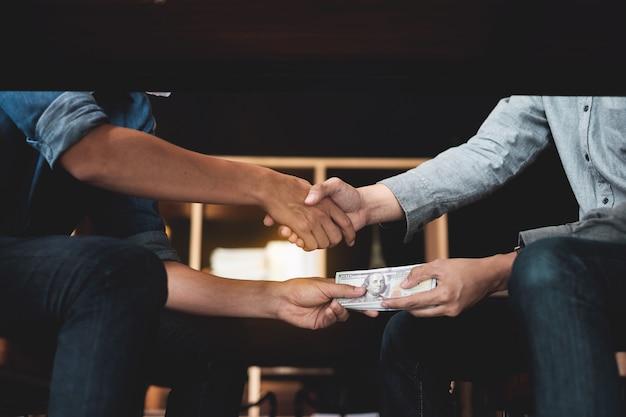 Empresários apertando as mãos com dinheiro suborno sob a mesa.