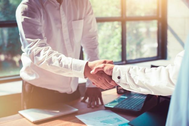 Empresários apertando as mãos no escritório.